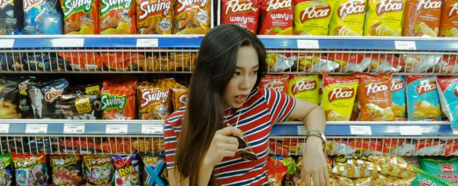 girl standing in front of food shelf
