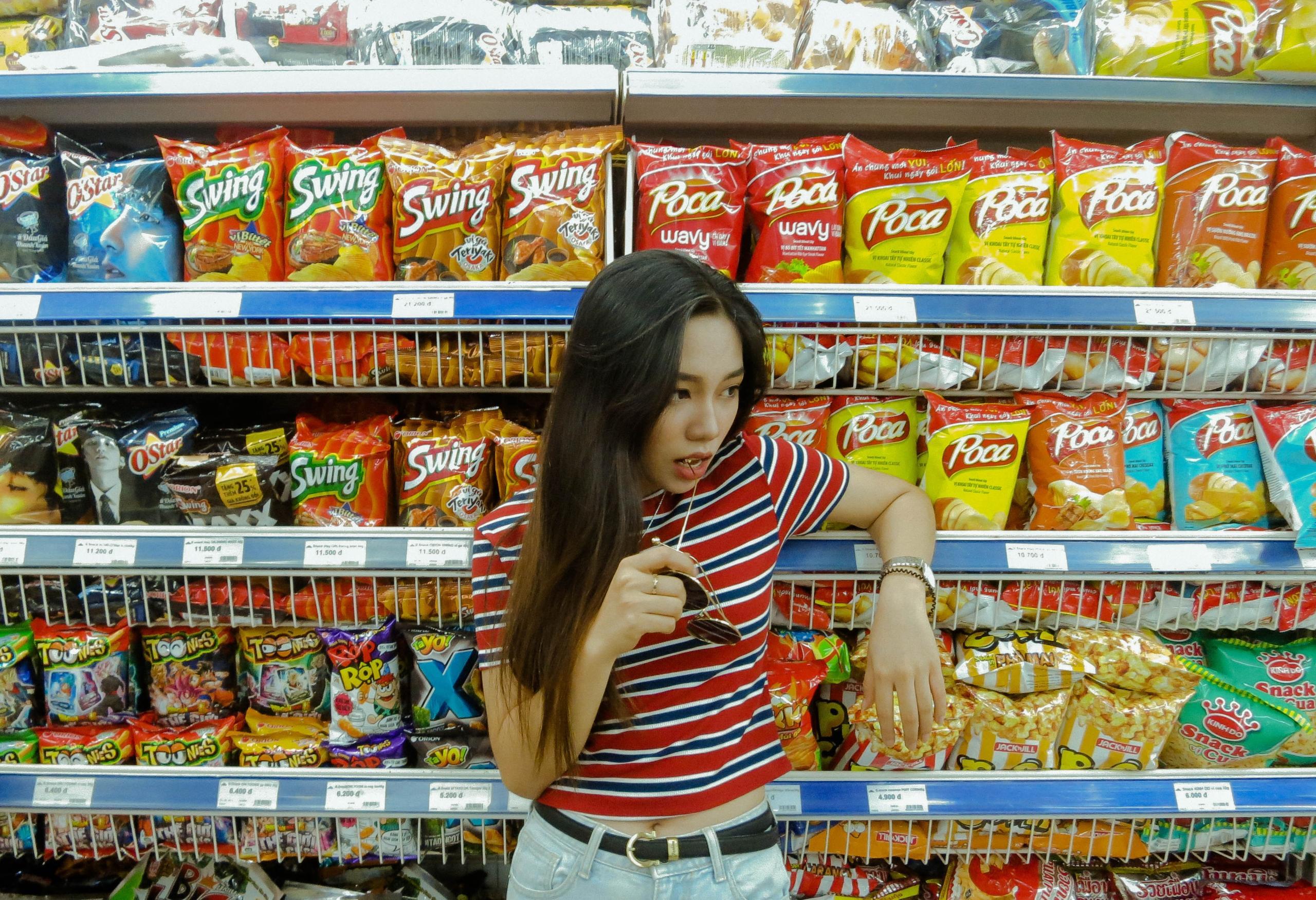 girl standing in front of food shelf